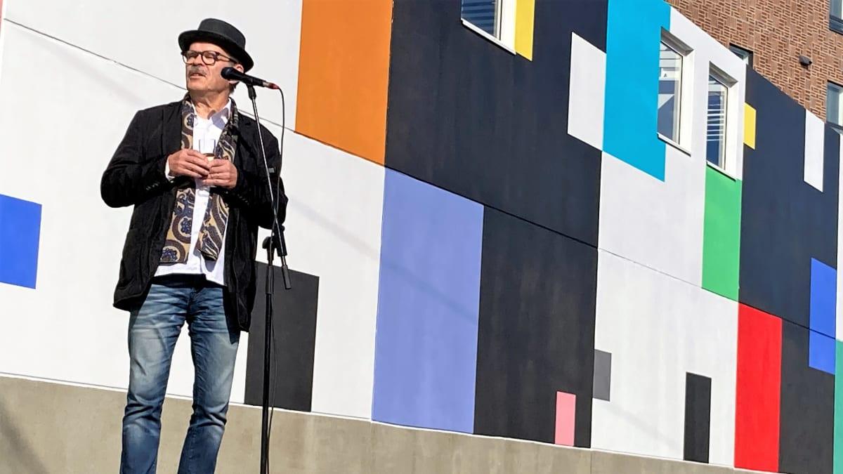 Taiteilija Veikko Törmänen maalaamassa muraalin edessä.