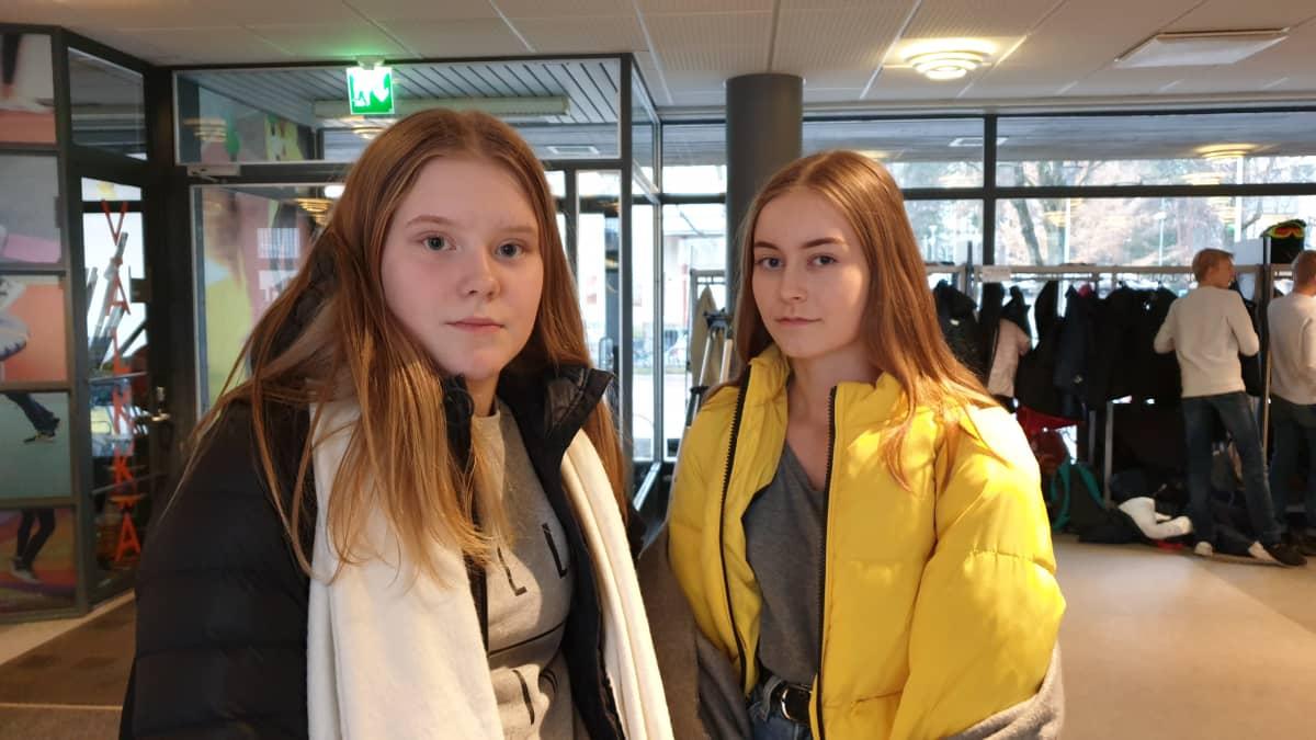 Kaksi tyttöä seisoo koulun aulassa