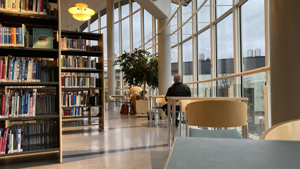 Kuvassa kirjasto ja asiakkaita
