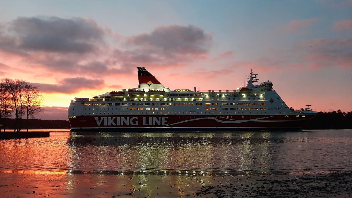 Viking Lines passagerarfärja Amorella glider förbi Folkparkens badstrand i Åbo en tidig morgon då morgonsolen lyser upp allt i gult och orange.