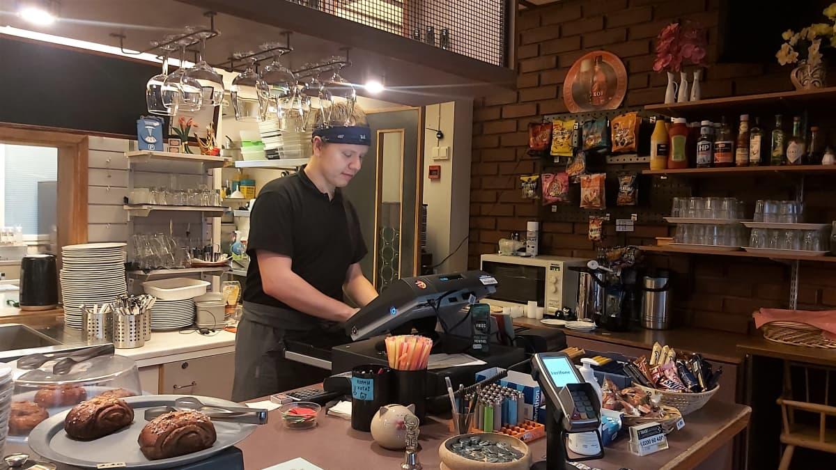 Ravintolatyöntekijä Ville Laihia palvelee asiakasta Ravintola Ukko-Pekassa.