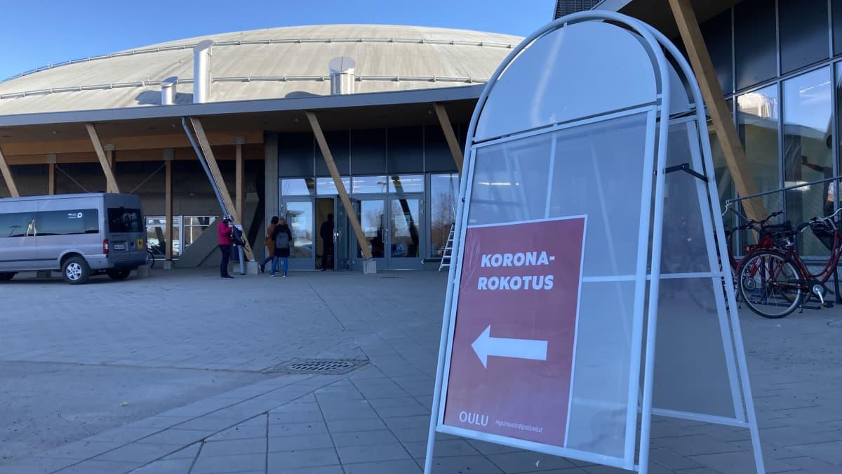 Ohjeviitta koronarokotuksiin Ouluhallin edustalla.