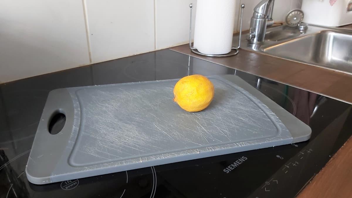 Vanha sitruuna nököttää kuluneella leikkuulaudalla.