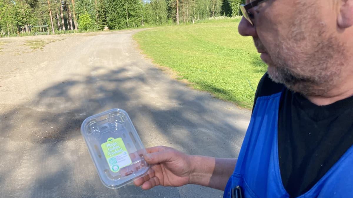 Kari Vauhkonen esittelee kierrätysmuovista tehtyä marjarasiaa.