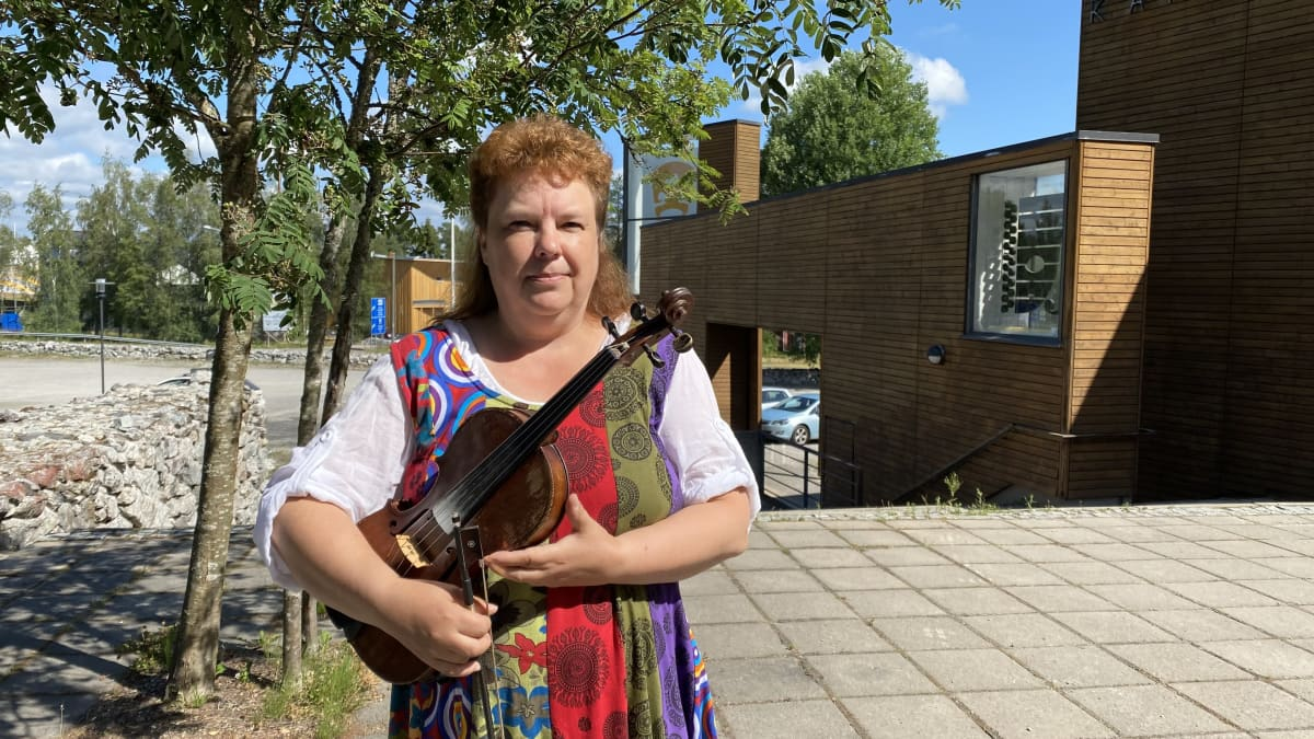 Anneli Aho pitelee viulua käsissään ja on pukeutuneena värikkääseen esiintymisasuun. Taustalla on Kaustisen Kansantaiteenkeskuksen rakennus