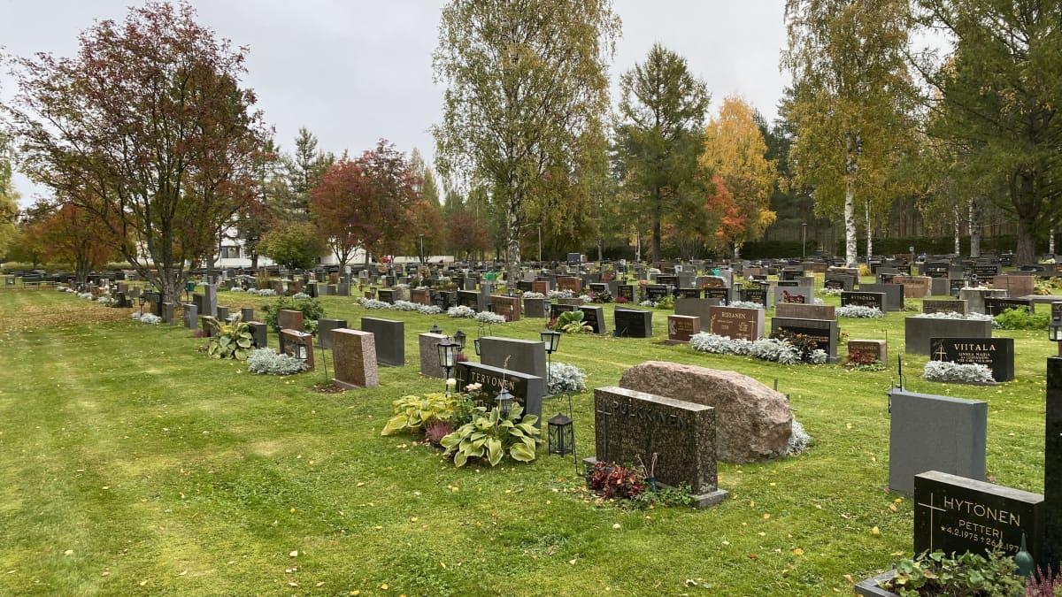 Hautakiviä on siisteissä riveissä syksyisellä hautausmaalla.