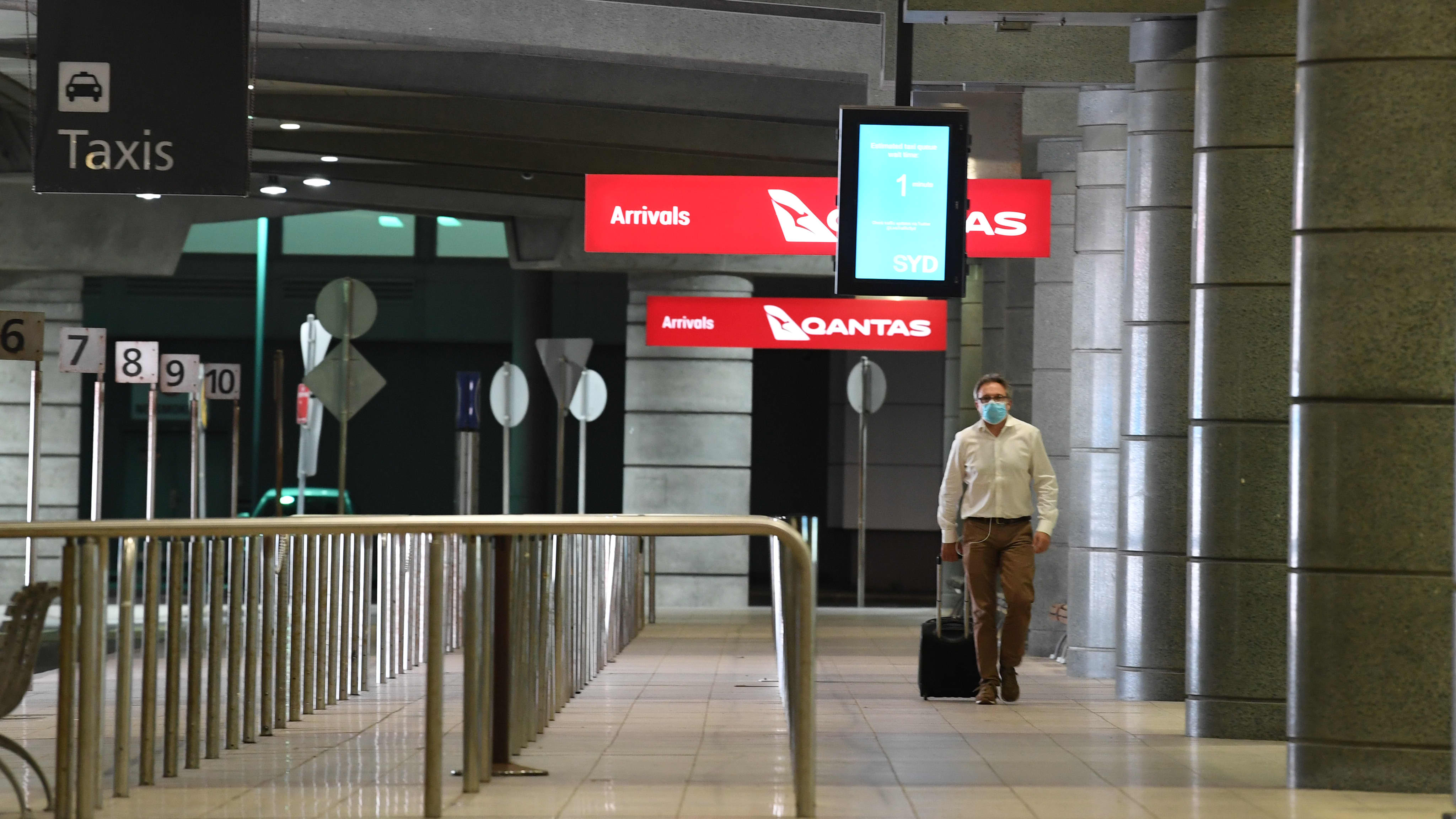 Matkustaja kävelee perässä vedettävän laukun kanssa lentokentällä.