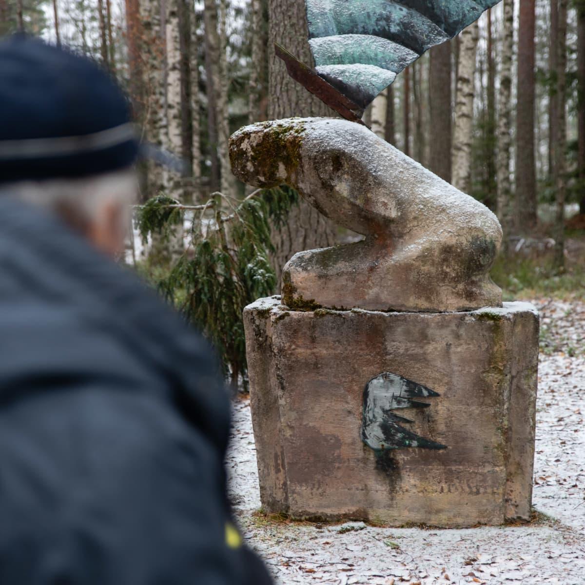 Matti Hjerppe katselee Rukoileva enkeli -patsasta Rauhan hautausmaalla.