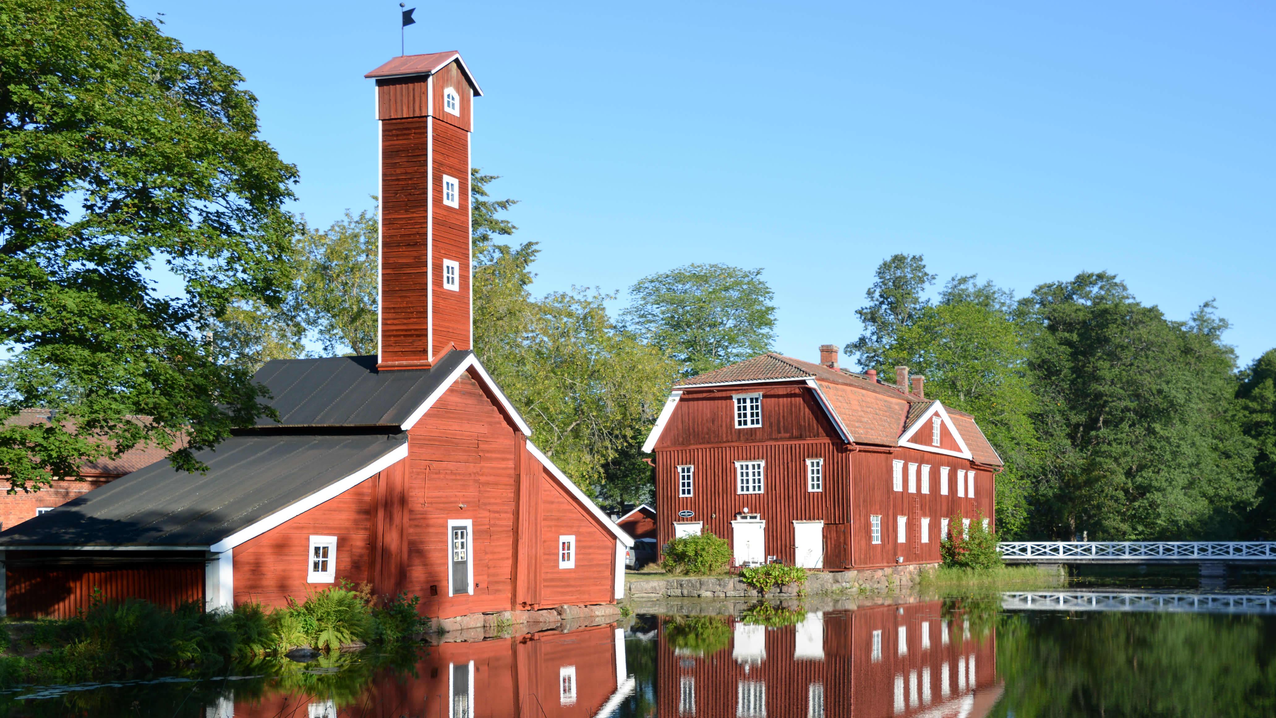 Två röda träbyggnader vid vatten, somrigt.