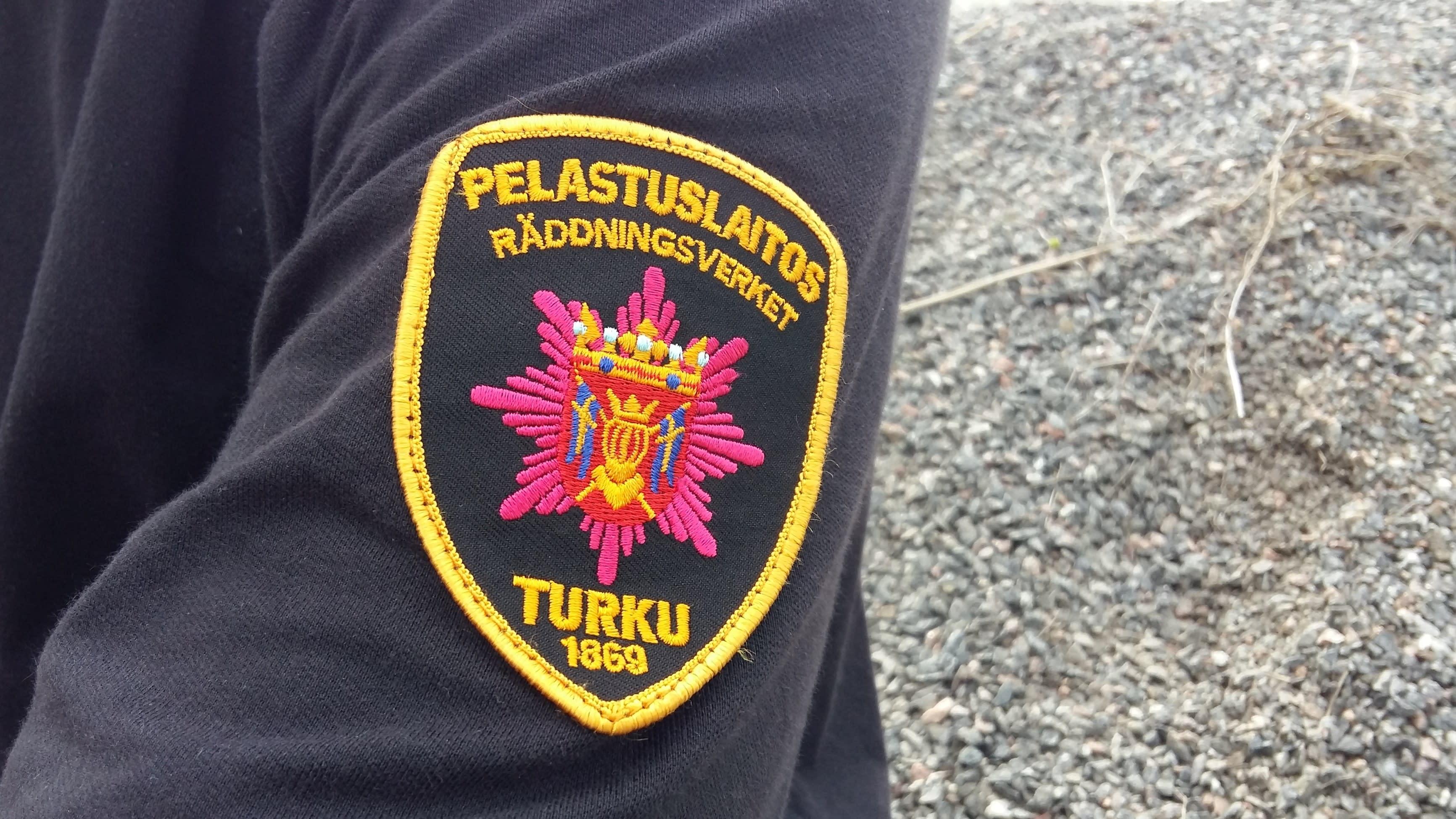 Pelastajan paidan hiha, jossa Varsinais-Suomen pelastuslaitoksen merkki.