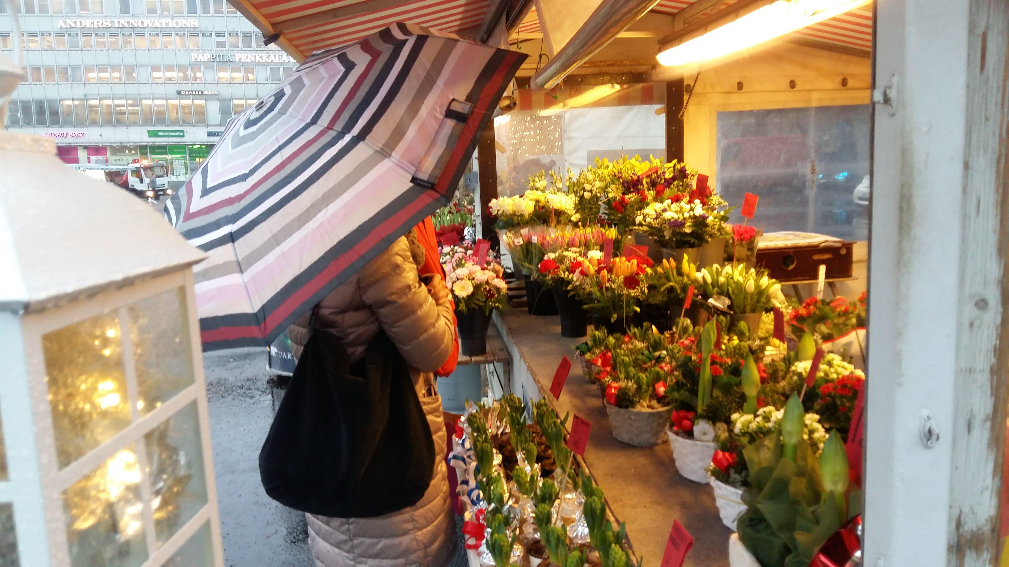 Nainen sateenvarjon kanssa torikojulla, jossa joulukukkia ja -valoja