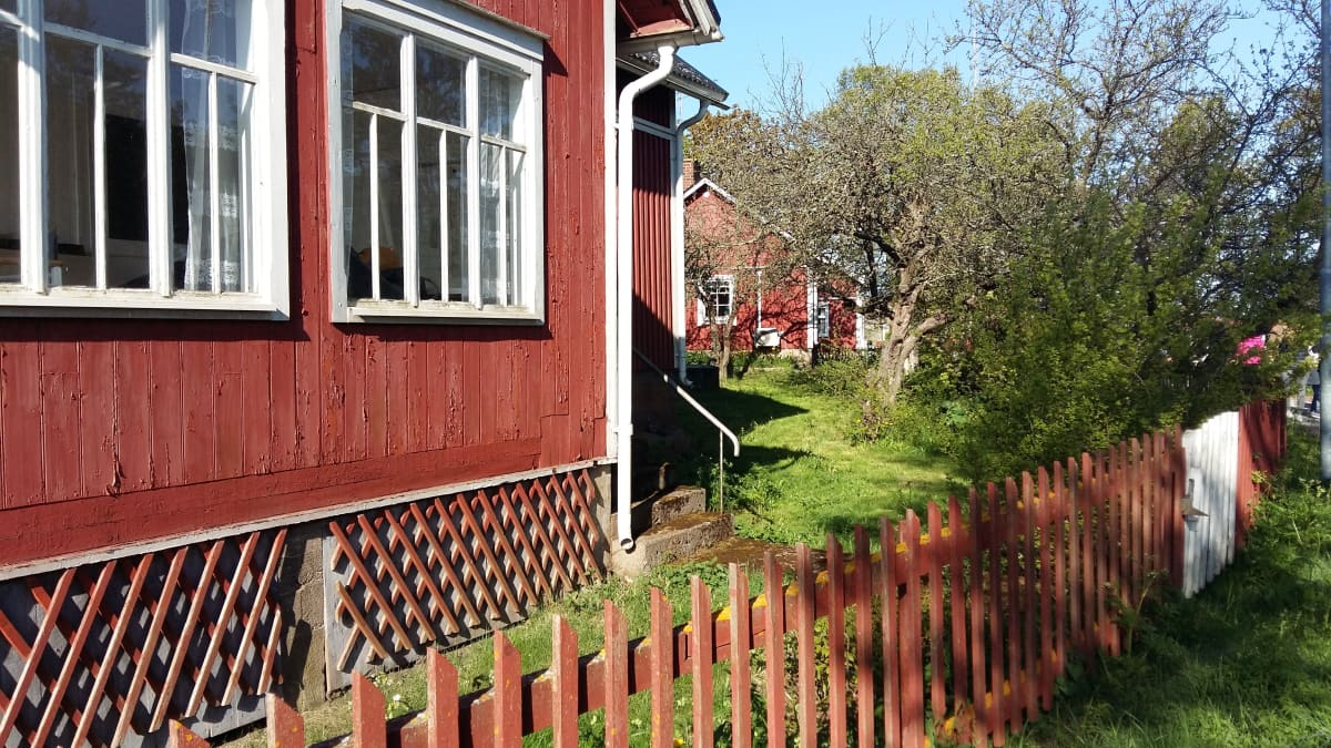 En röd stuga med vita knutar på Utö.