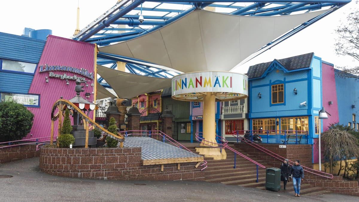 """En ingång till en nöjespark. På väggen och på en skylt står det """"Linnanmäki"""" och """"Borgbacken""""."""