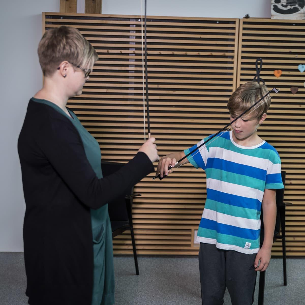 Opettaja ja näppäripelimanni harjoittelemassa jousikäden asentoa.