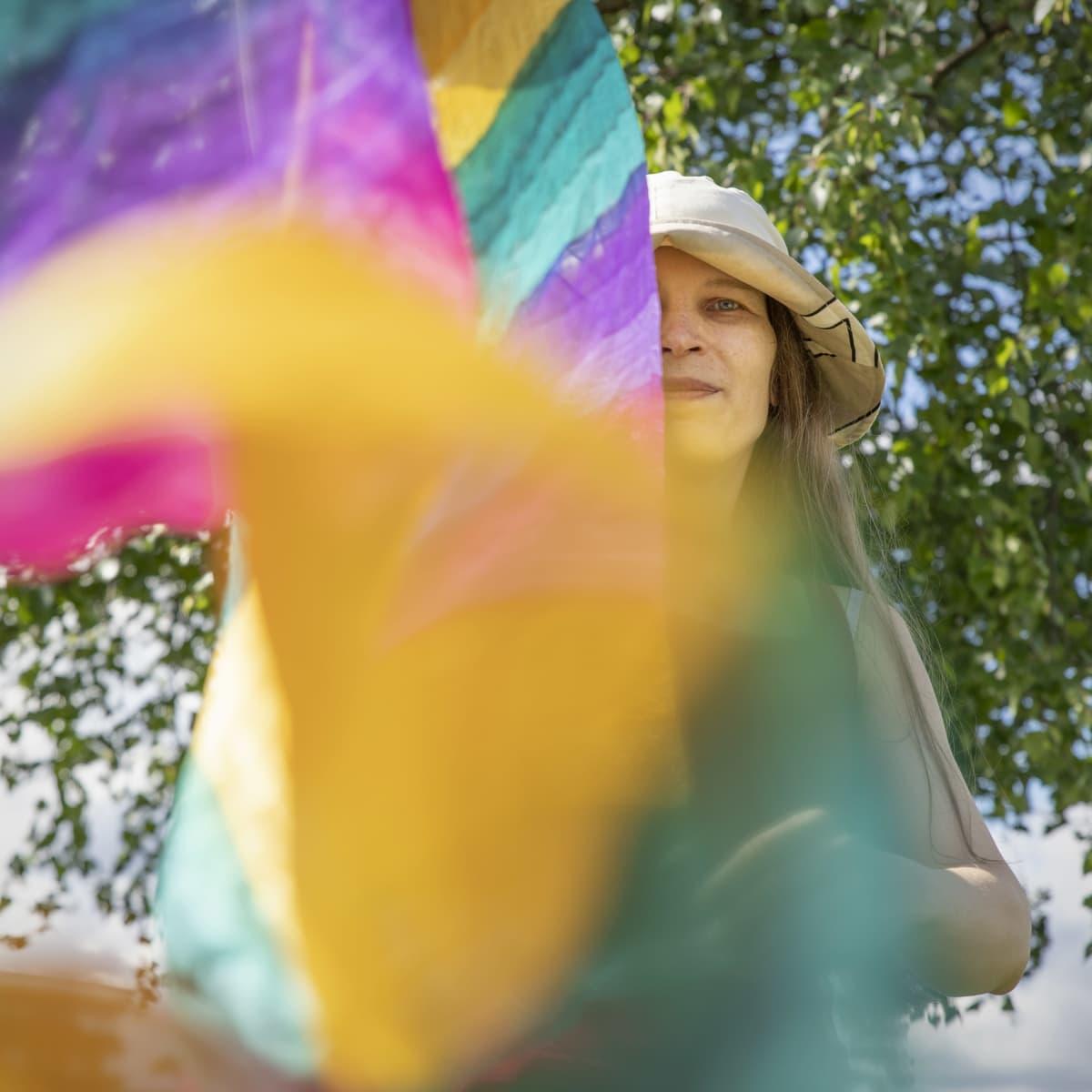 Alia Dannenberg ja tuulessa hulmuava sateenkaarihuivi.