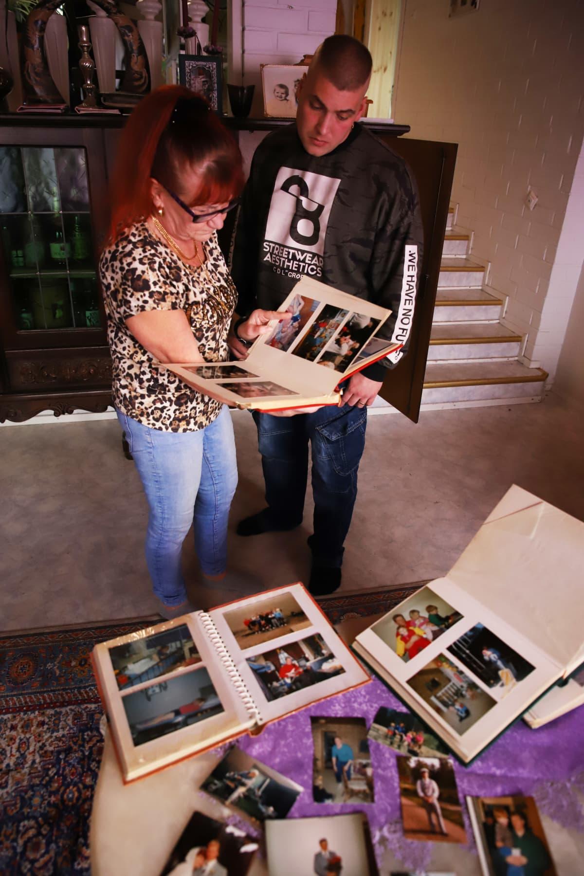 "Vuonna 1995 Kotkassa surmatun Osmo ""Lusu"" Ahlqvistin ex-vaimo Marita Ahlqvist ja poika Tomi Ahlqvist katselevat vanhoja valokuvia."