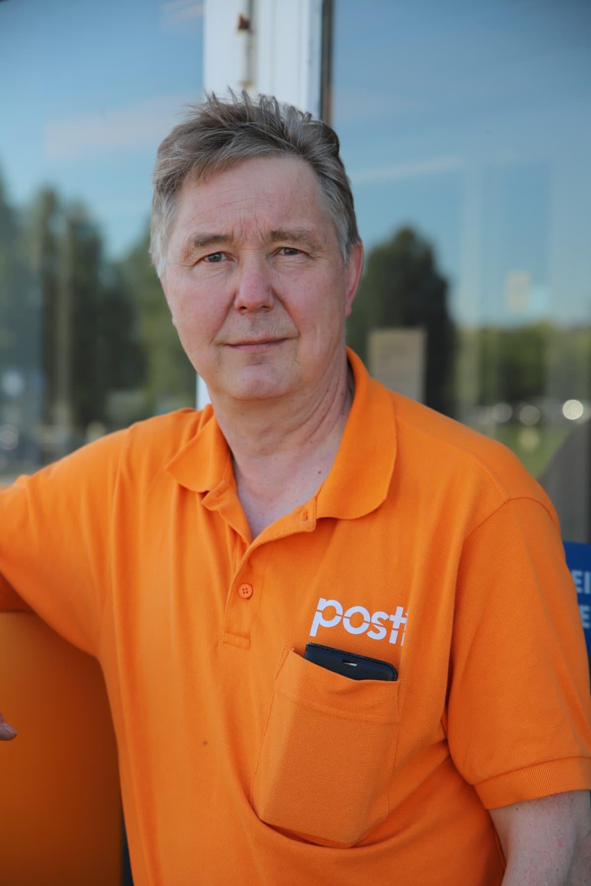 Postin työntekijä Jyrki Sutinen nojaa Rovaniemen postin seinään.