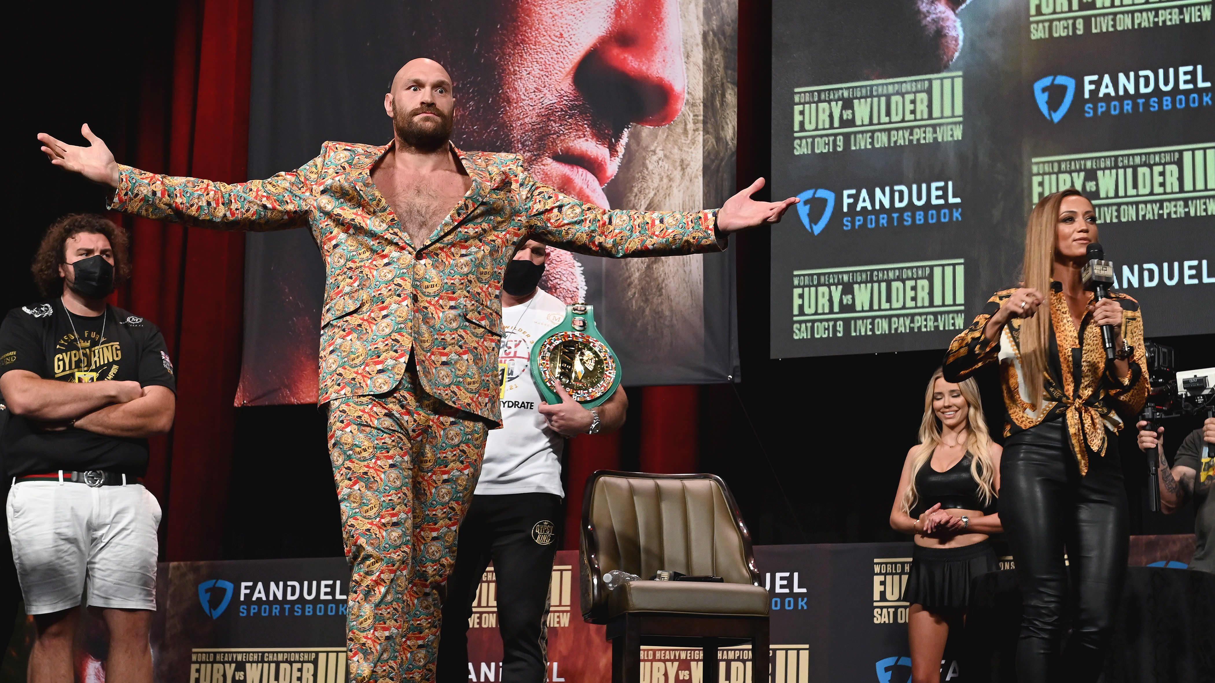Tyson Fury värikkäässä asussa levittelee käsiään.