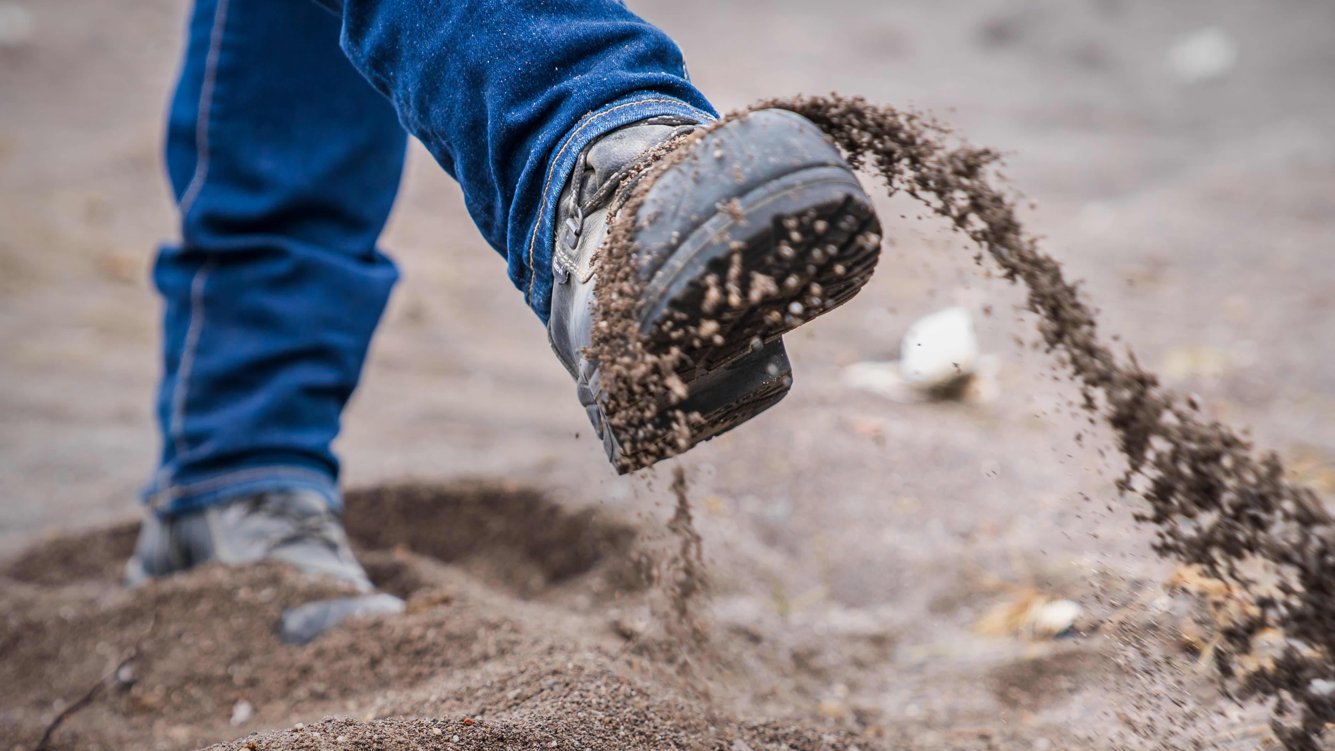 Jalka potkaisee kaatopaikan pohjakuona-ainesta.