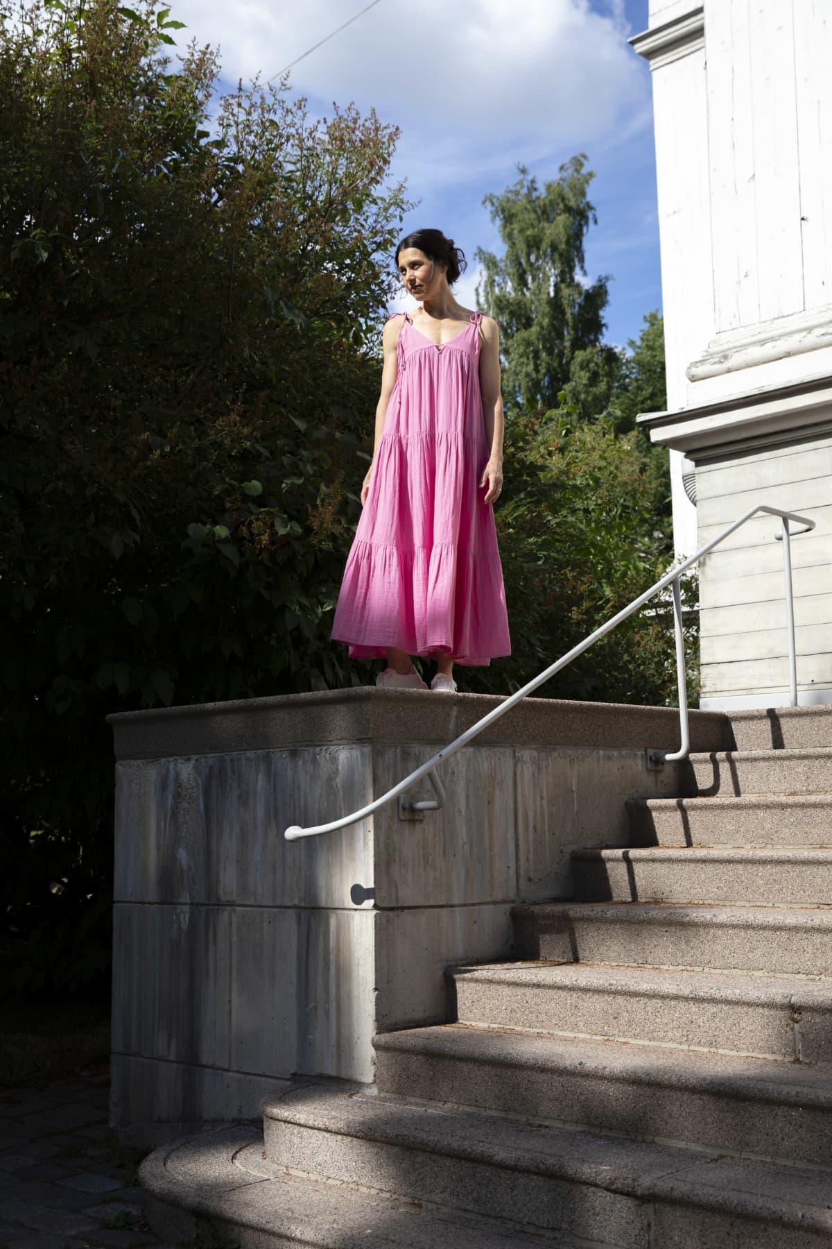 Nainen vaaleanpunaisessa kesämekossa seisoo auringossa rakennuksen isolla porrastasanteella. Aurinko paistaa, nainen katsoo vasemmalle.