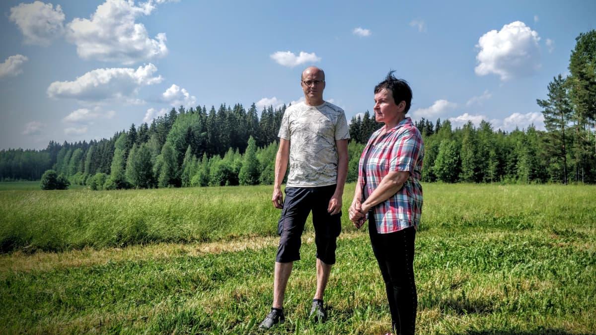 Seppo Rantanen ja Lea Ala-Outinen-Viinanen seisovat peltoaukean laidalla.