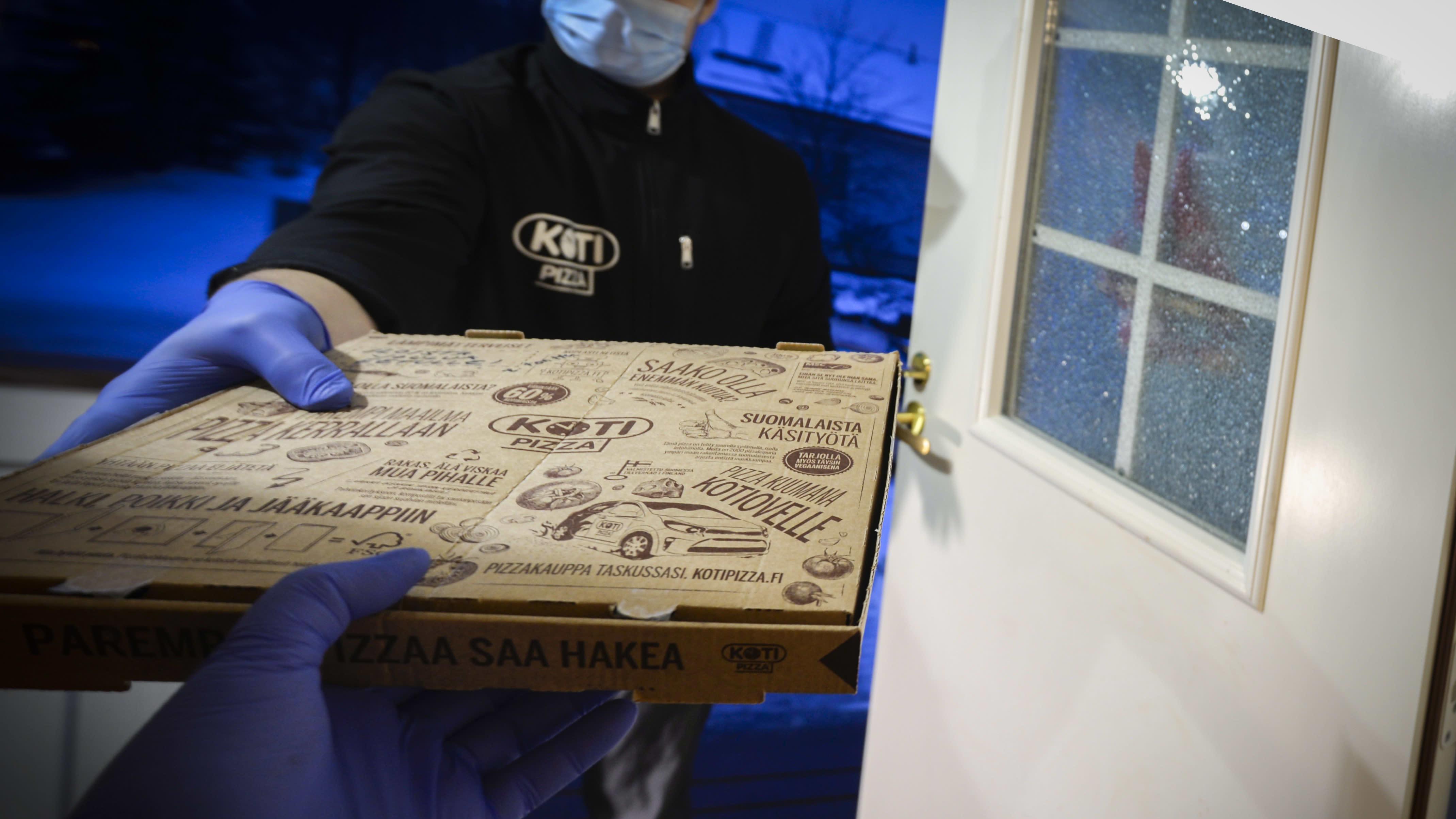 Kotiin tuodaan pizza ravintolasta. Koronan aikaan maski kasvoilla.