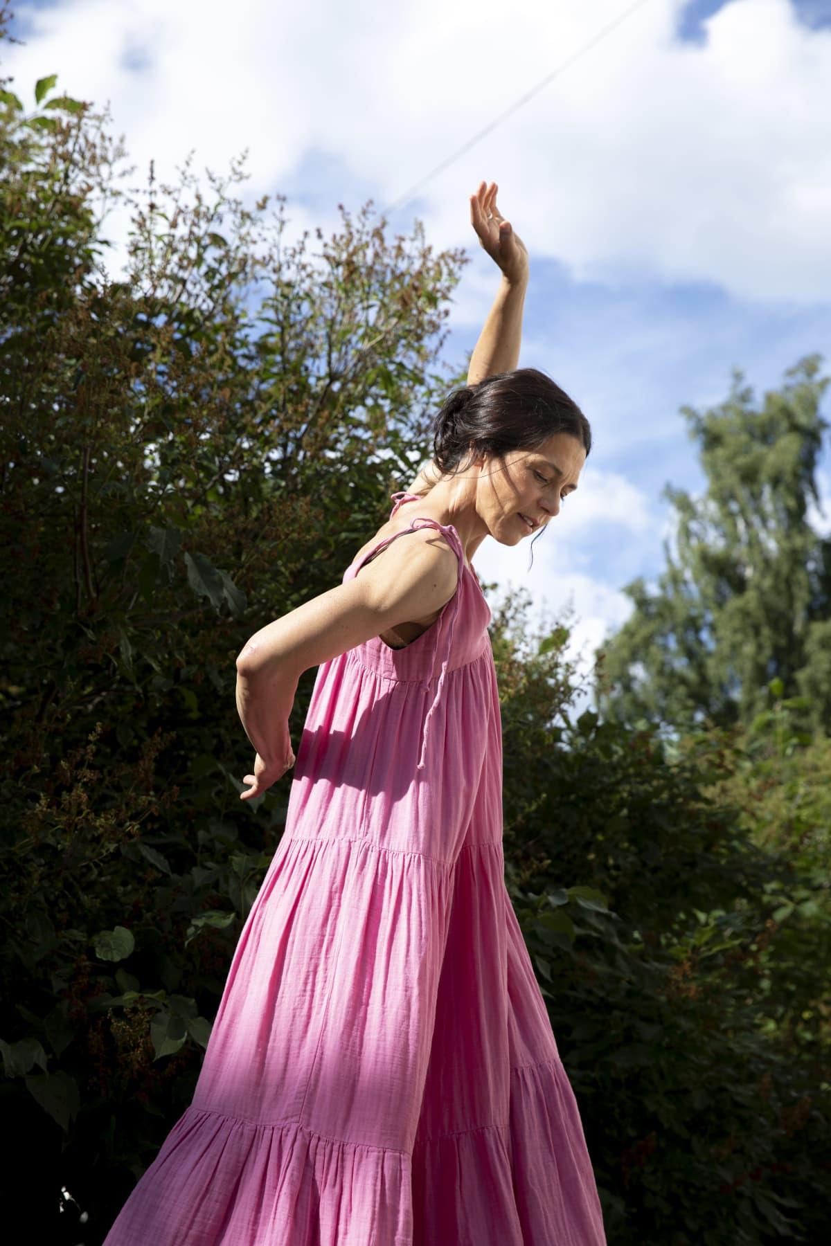 Nainen vaaleanpunaisessa kesämekossa on keskellä tanssillista liikettä. Toinen käsi osoittaa kohti taivasta, otinen on selän takana. Taustalla lehtiä ja sininen taivas.