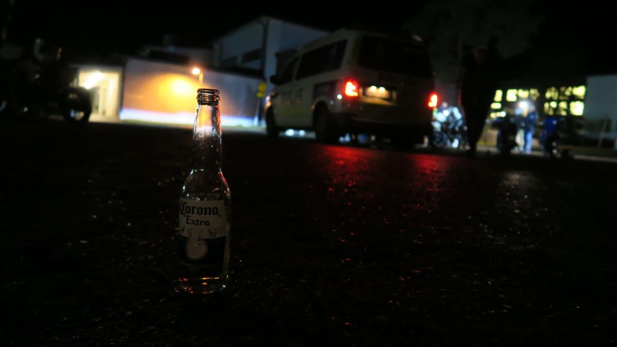 Corona-pullo asvaltilla pimeällä koulun pihalla.