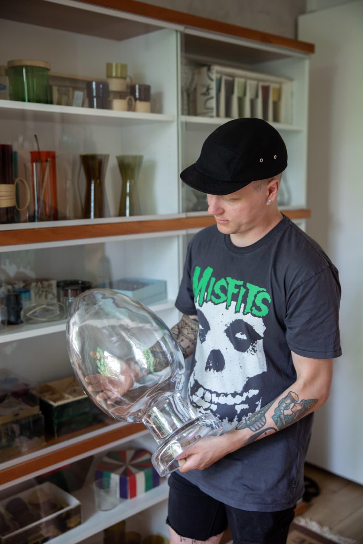 Mies esittelee ovaalin muotoista lasista ja suurta design-esinettä. Taustalla hylly, jossa on design-esineitä.