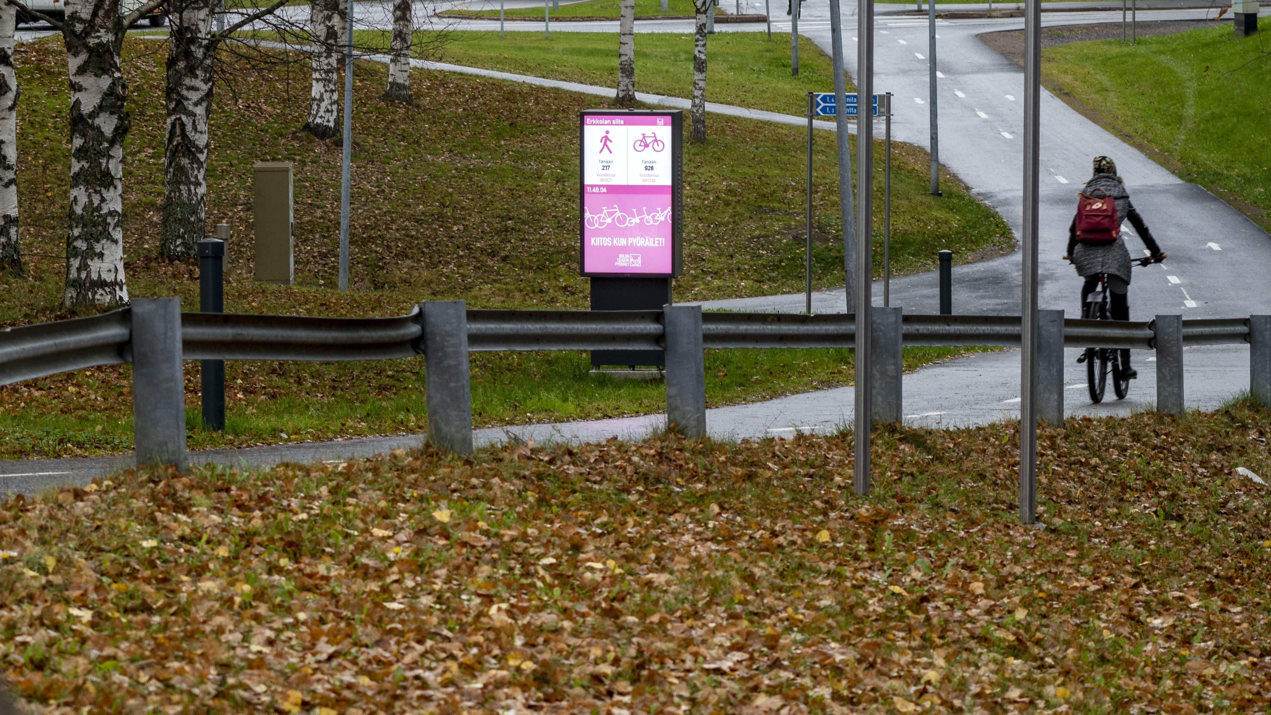 Pyöräilijä ajaa Oulussa Erkkolansillan digitaalisen opaseteen ohi.
