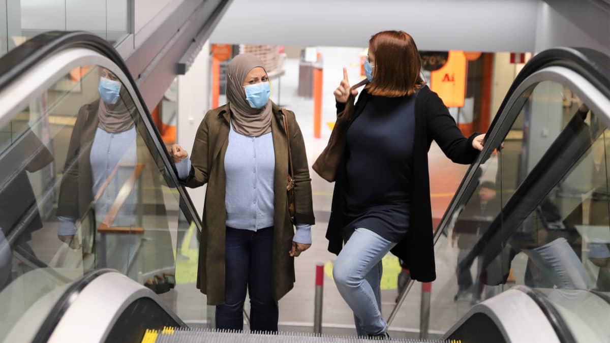 Irakista Suomeen tullut Roqaya Al-Anbagi ja suomalainen Paula Malan seisovat liukuportaissa Trion kauppakeskuksessa Lahdessa.