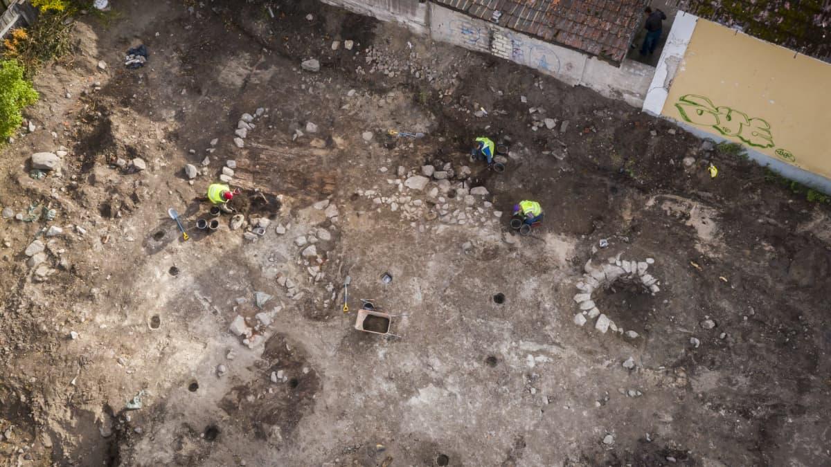 Näkymä ylhäältä ilmasta Feeniksin tontin arkeologisille kaivauksille. Oikealla puolella näkyy kaivo ja vasemmalla rakennuksen perustuksia.