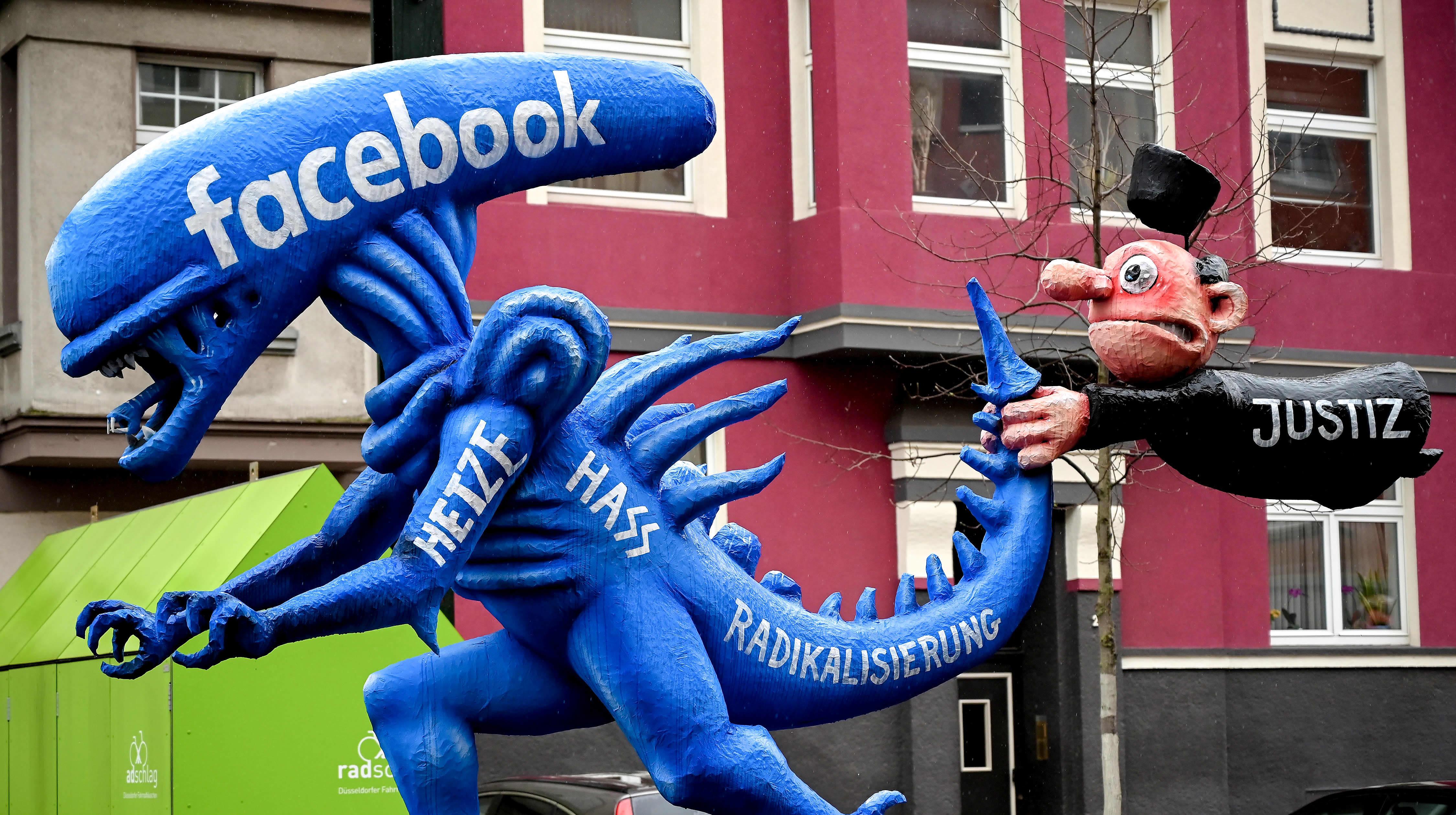 Sinisen alien patsaan hännästä pitää kiinni lennossa oleva tuomarihahmo. Alien edustaa Facebookkia ja tuomari oikeutta.