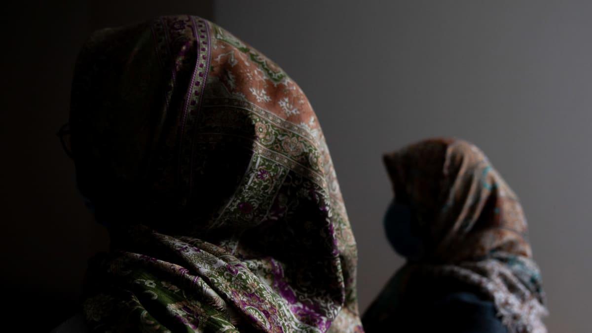 Kaksi afgaani naista huivit päässä ja kasvot varjossa.