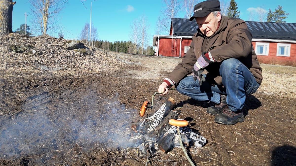 Mauri Laitila paistaa makkaraa nuotiolla Keskikylän nuorisoseuran pihalla