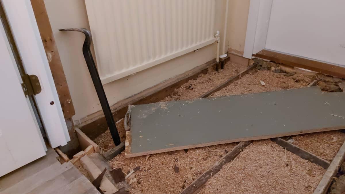 Sorkkarauta nojaa seinää, vieressä avattu lattia, purueristeet mäkyvissä