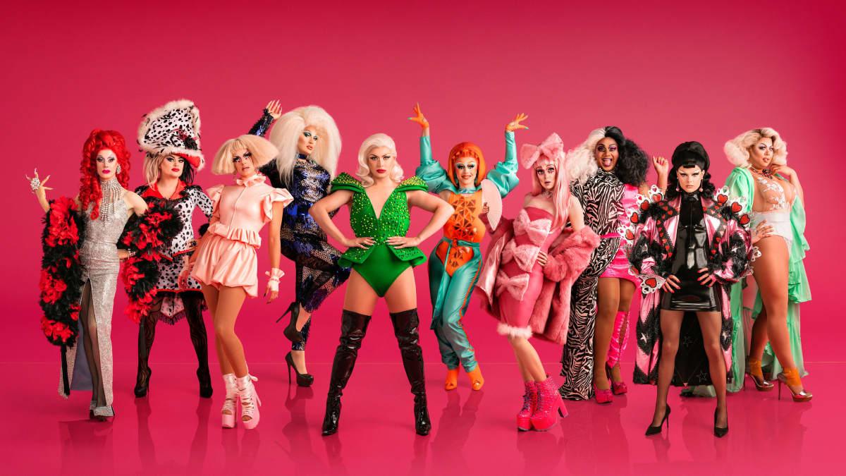 RuPaul's Drag Race UK -kilpailijat punaista taustaa vasten.