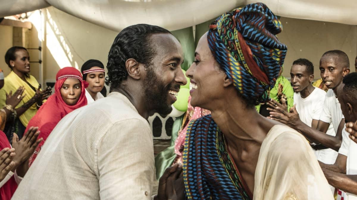 Mies ja nainen kasvot lähekkäin, taustalla taputtavia ihmisiä. Elokuvasta Guled & Nasra.