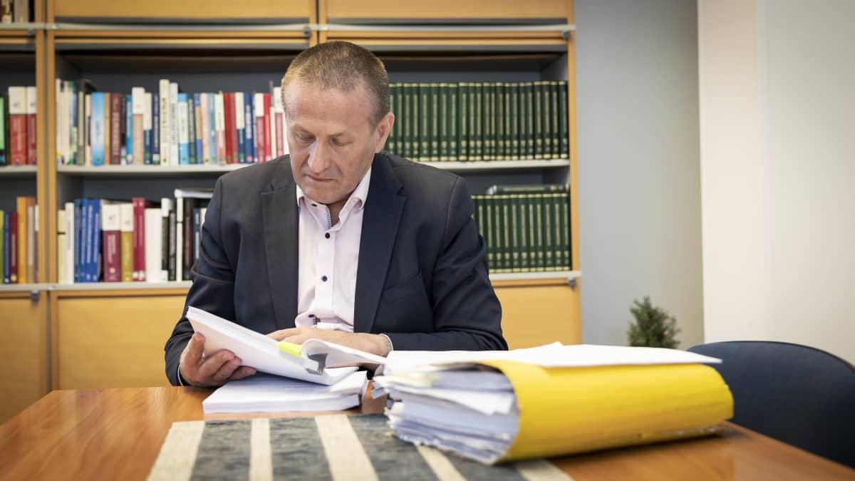 Mies selailee paperinivaskaa pöydän ääressä.