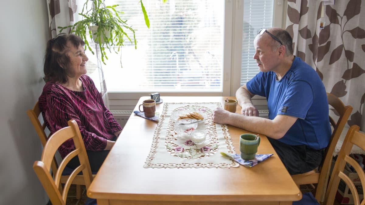 Eila Juurinen kestitsee kyläavustaja Rami Hantulaa joka auttoi kodin siivouksessa,