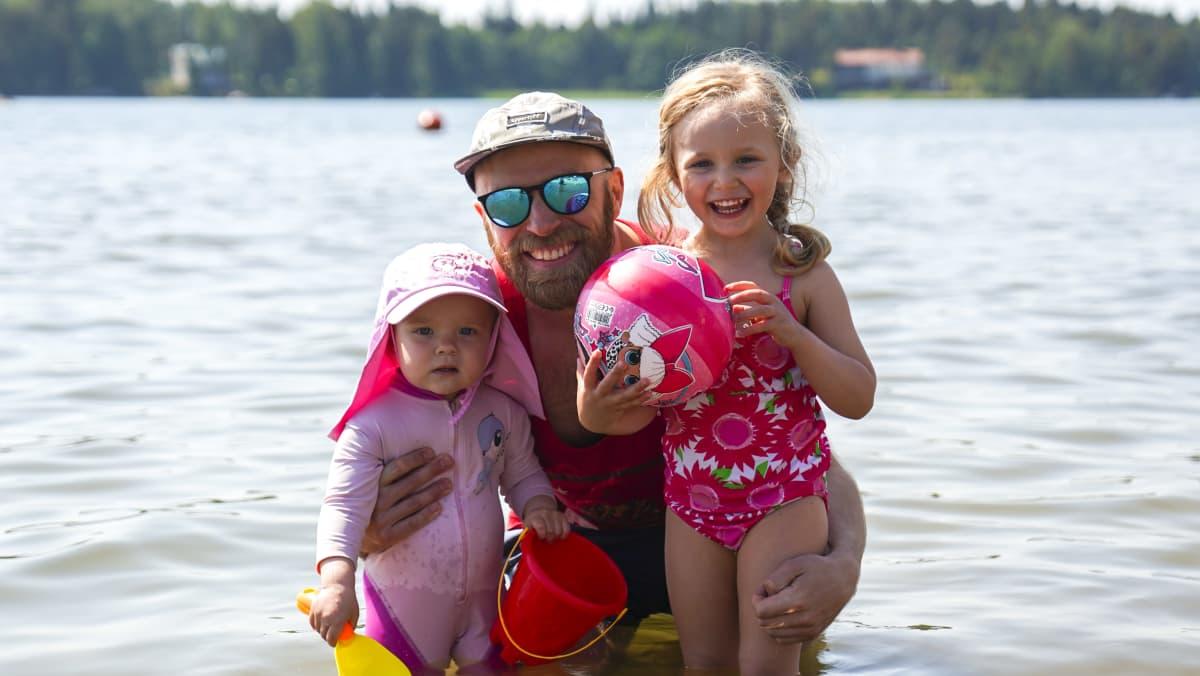 """Jarkko Vilkki luottaa janojuomana veteen, koska """"se on vanhin voitehista."""" Mai Vilkki (vasemmalla) osaa tehdä selväksi, että hän haluaa veteen uimaan. Viena Jauhianen (oikealla) haluaa poseerata myös tässä kuvassa, koska hän osaa sen hyvin."""