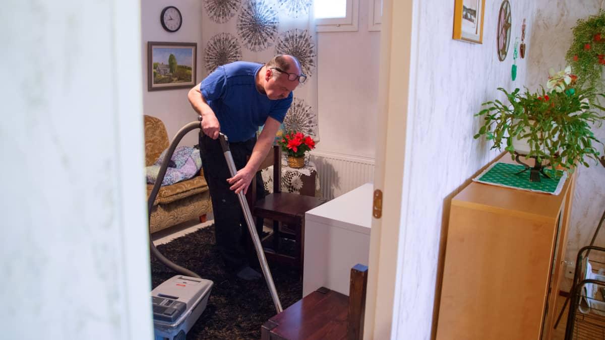 Kyläavustaja Rami Hantulan tehtäviin kuuluu ikäihmisten kodin siivoaminen.