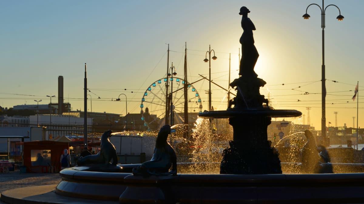 Havis Amanda -patsas kuvattuna nousevaa aurinkoa vasten. Taustalla Helsingin Kauppatori.