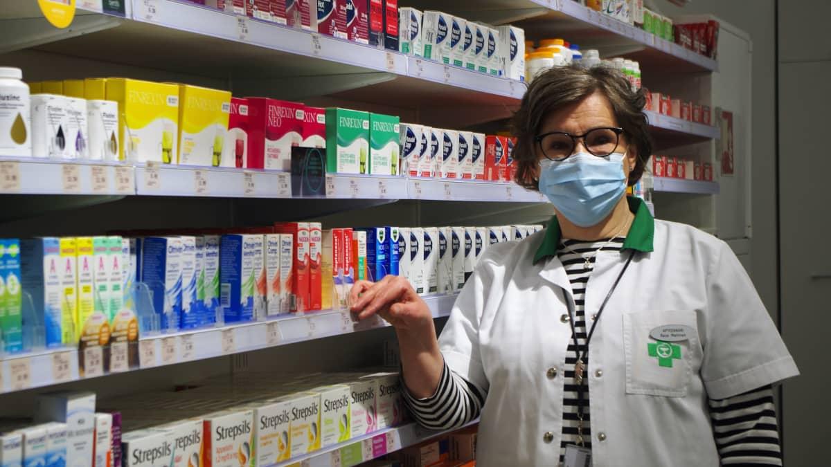 Seinäjoen keskusapteekin apteekkari Raija Mattinen seisoo itsehoitolääkehyllyn edessä.