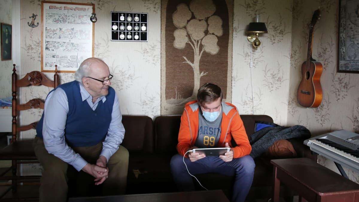 Markku Pihlajamaa seuraa vieressä, kun digineuvoja  Olavi Helernius laittaa Markon tietokoneen kuntoon.