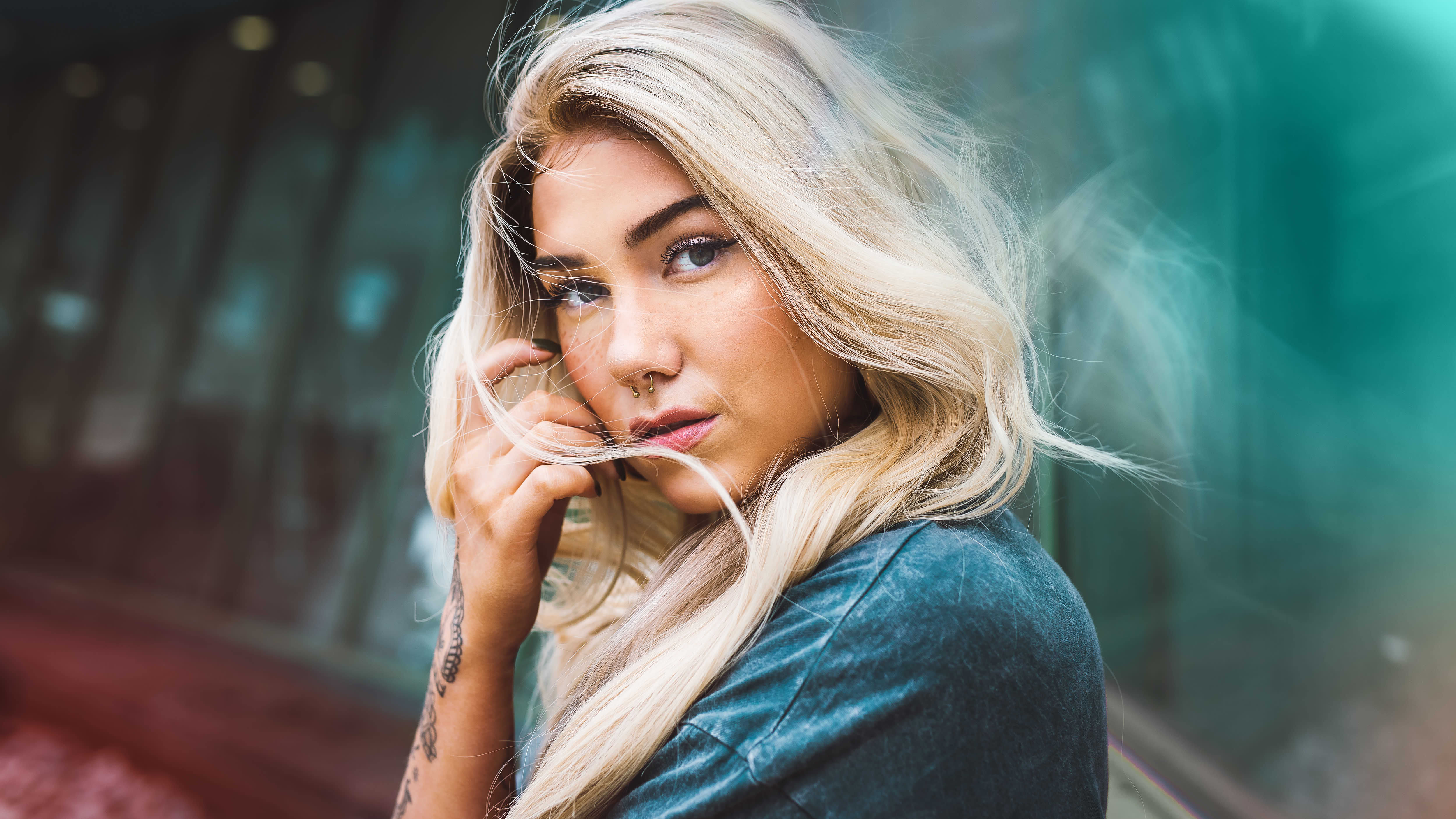 Vaaleahiuksinen laulaja Evelina katsoo tuulessa heiluvien hiustensa takaa kameraan. Hän seisoo kameraa kohti sivuttain ja nojaa toista kättään kevyesti poskeensa.
