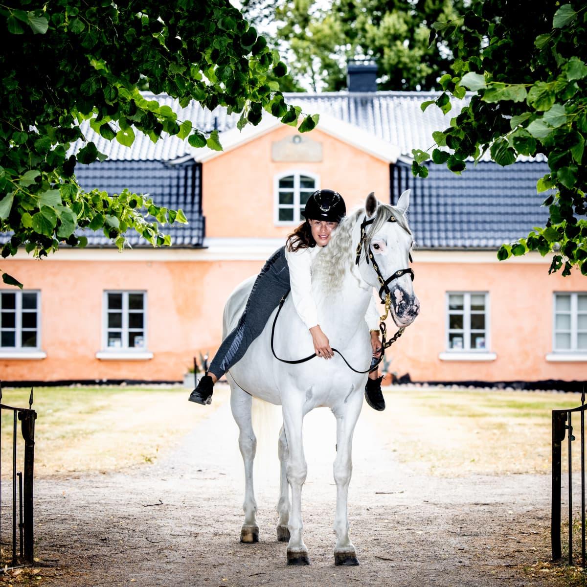 Alisa Redman andalusianhevosensa kanssa Tuomarinkylän kartanon puistossa.