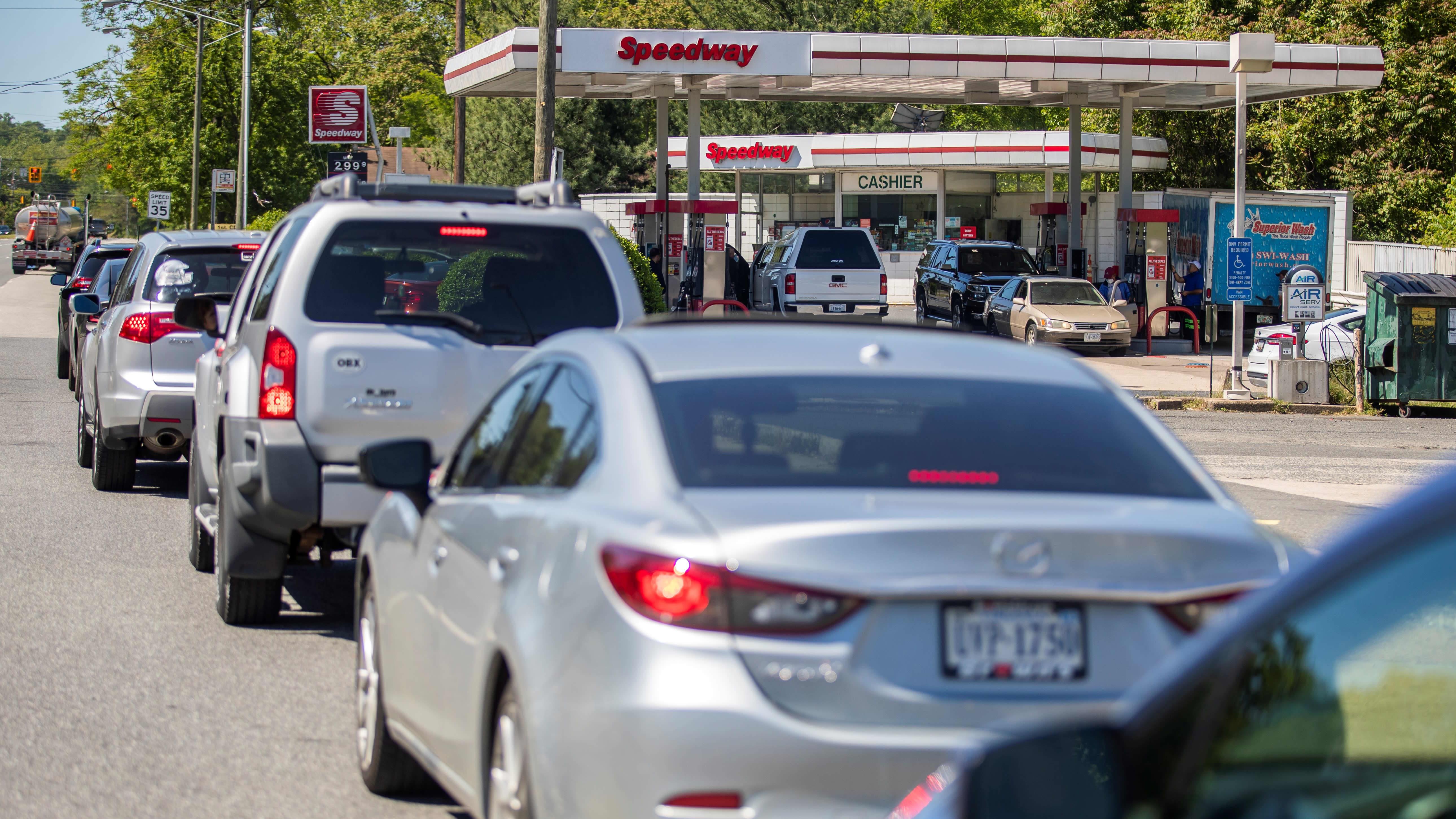 Pitkä autojono odottaa pääsyä bensiiniasemalle.