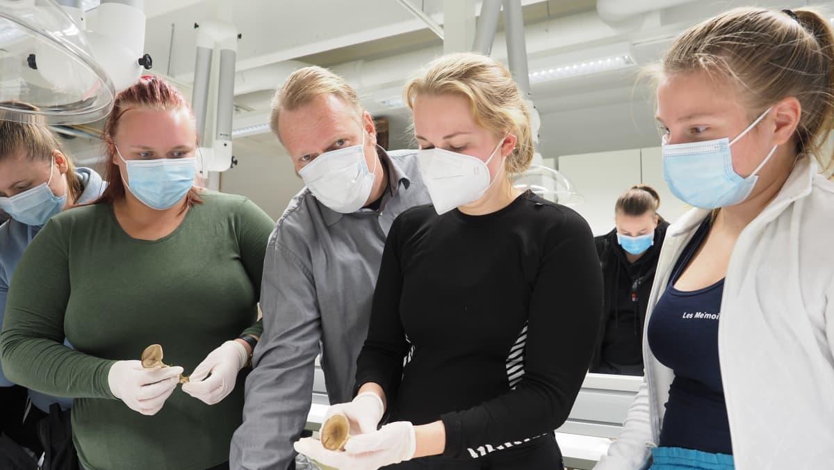 Itä-Suomen yliopiston opiskelijoita ja opettaja Vesa Paajanen tutustumassa sieniin oppitunnilla.