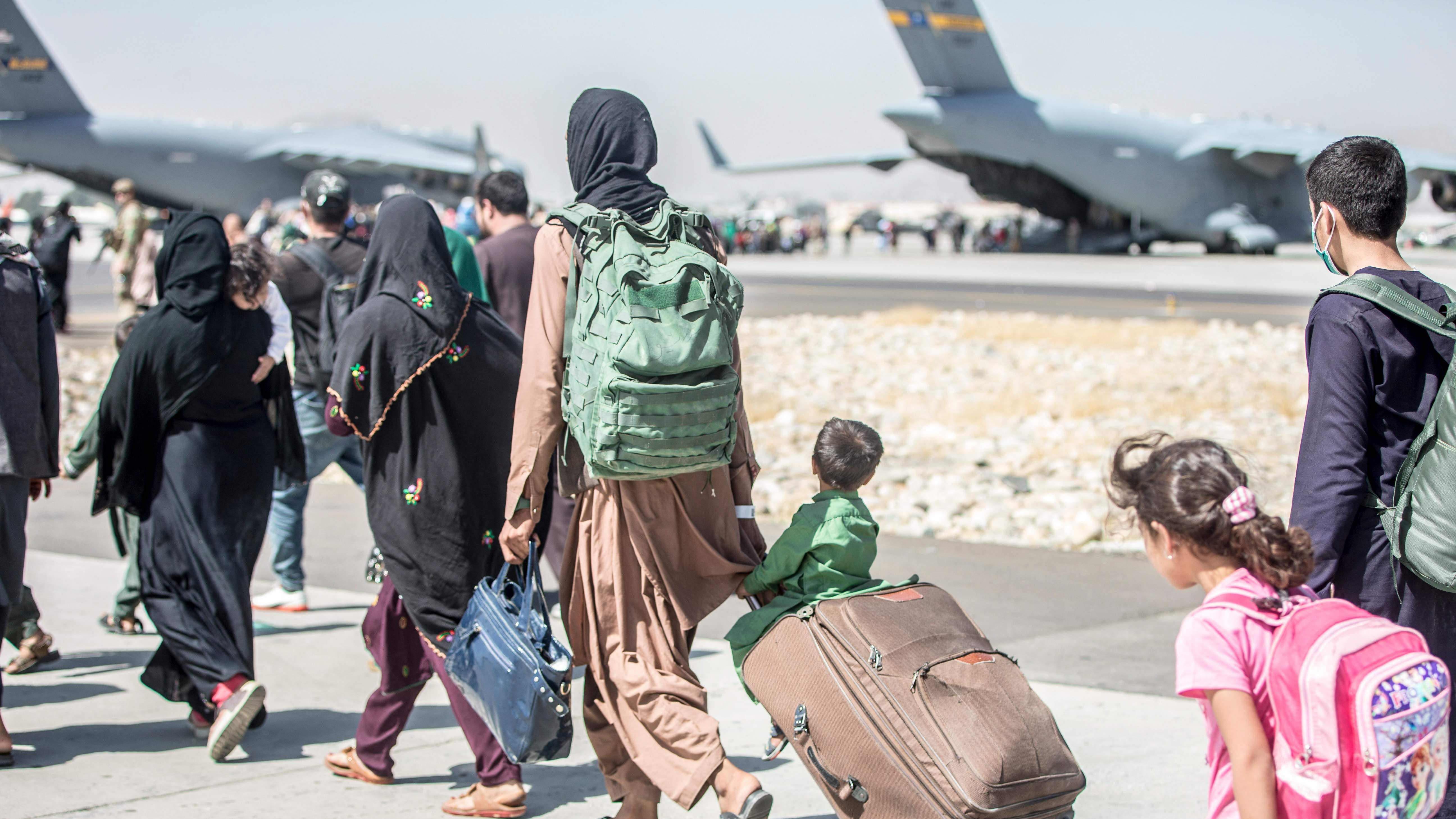 Afghaner på väg att evakueras på flygplatsen i Kabul den 24 augusti 2021. Ett litet barn sitter på en resväska och blickar mot ett av flygplanen.
